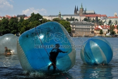 Tourists play in zorb balls on the Vltava river