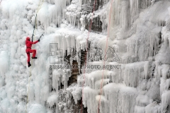 A man climbs up an artificial ice wall in Liberec